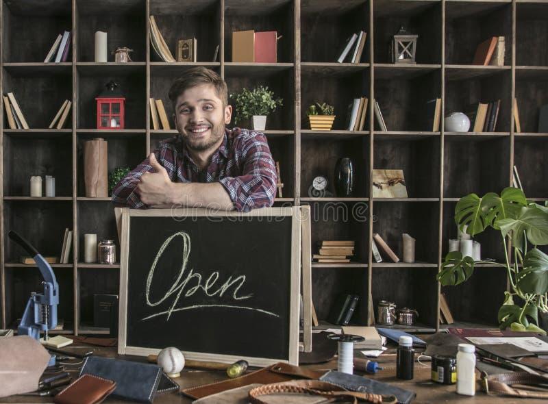 Lederhersteller des jungen Mannes, der bei Tisch nahe offenem Zeichen mit ledernen Werkzeugen steht lizenzfreie stockfotos