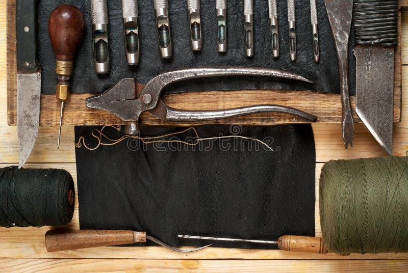 Lederne Handwerkswerkzeuge auf hölzernem Hintergrund Craftmans-Arbeitsschreibtisch Stück Fell und handgemachte Werkzeuge Beschnei stockfotografie
