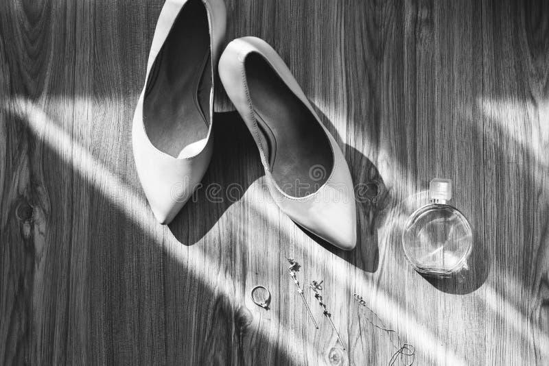 Lederne Hochzeitsschuhe der hohen Absätze auf dem hölzernen Hintergrund in den Sonnenstrahlen Modeschmuckohrringe und -armband mi lizenzfreie stockfotografie