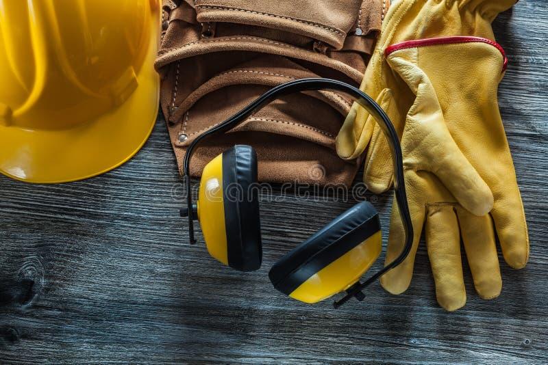 Lederne Schutzhandschuhe bedecken Werkzeuggurtohrenschützer auf hölzernem Brett mit einer Kappe stockfotos