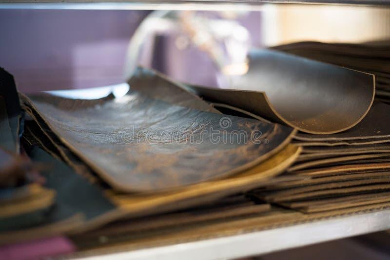Lederne Stücke des Schnittes sitzen sortiert und bereiten für Buchbinderei vor stockbilder