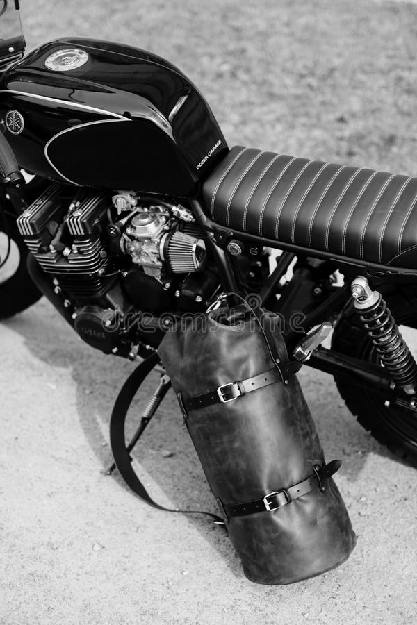 Lederner Rucksack nahe dem Motorrad Halb schwarzes Motorrad in der Garage Motorrad kaferacers stockbild