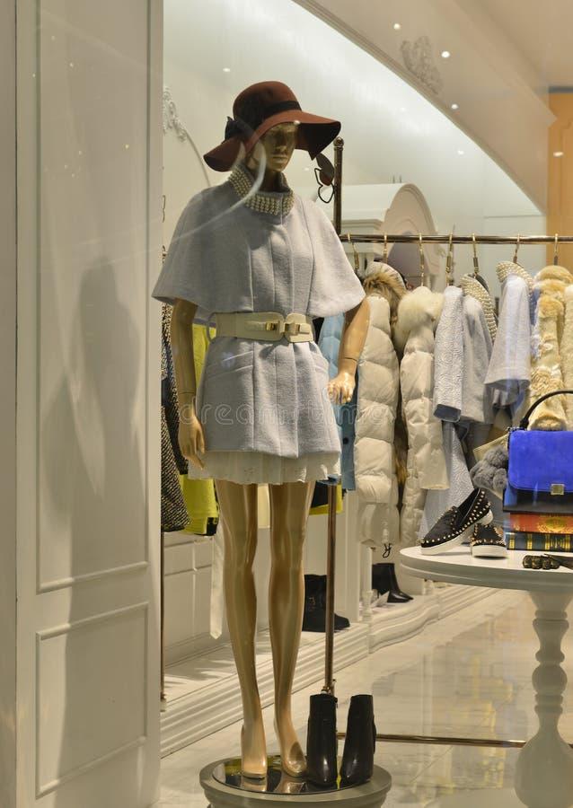 Lederstiefel und eine weibliche Mannequinabnutzungsbraunkappe in einem Modeshopfenster lizenzfreie stockbilder