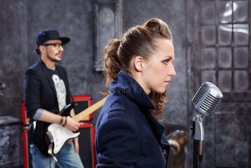 Ledningssångaren står på mikrofonen royaltyfria bilder
