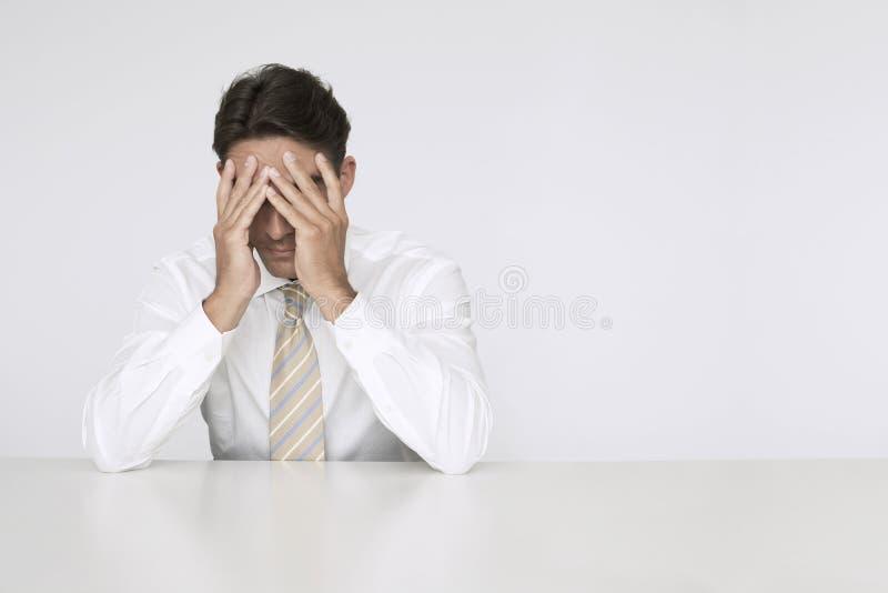 Ledsen affärsman Sitting At Desk i regeringsställning royaltyfria foton