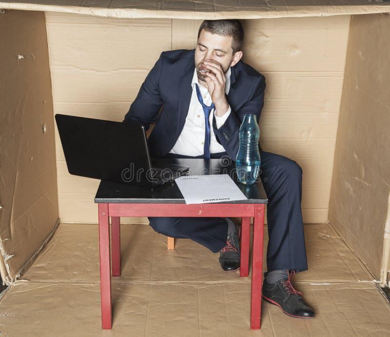 Ledsen affärsman som dricker alkohol royaltyfri fotografi