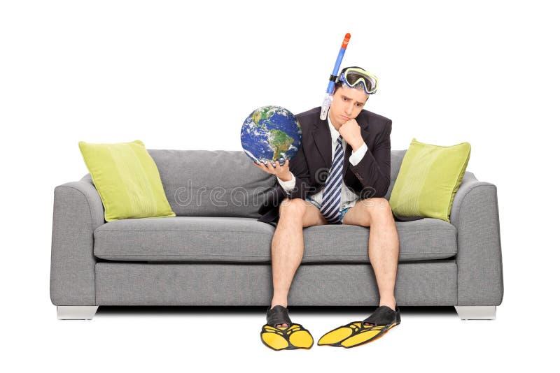 Ledsen affärsman som rymmer jorden och sitter på soffan royaltyfria bilder