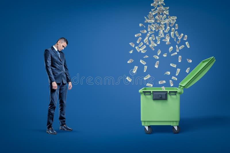 Ledsen affärsman som ser ner anseende bredvid öppen dumspter med regn av dollar som faller in i det royaltyfri illustrationer