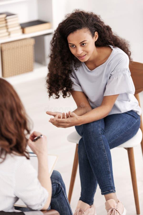 Ledsen amerikansk flicka med sociala problem under psykoterapi royaltyfri bild