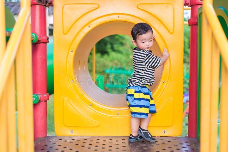 Ledsen asiatisk pojke som spelar i gul tunnel på lekplatsen med su royaltyfria bilder
