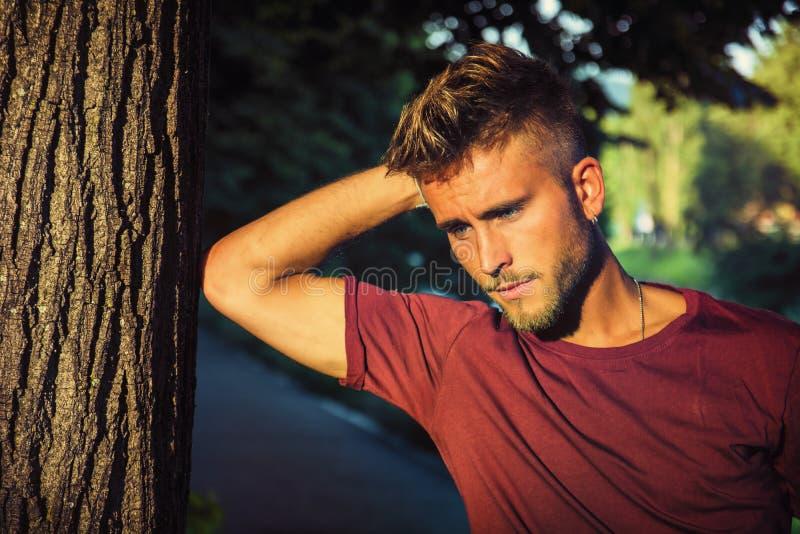 Ledsen bekymrad blond ung man mot träd arkivfoton