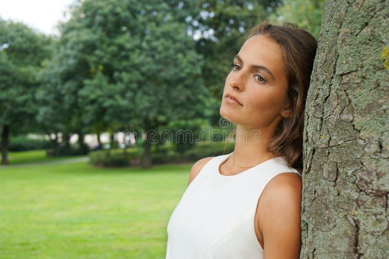 Ledsen benägenhet för ung kvinna mot träd arkivfoto