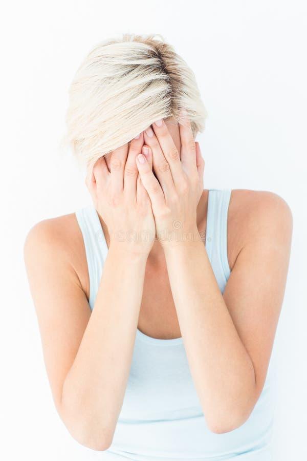 Ledsen blond kvinnagråt med huvudet på händer royaltyfri fotografi