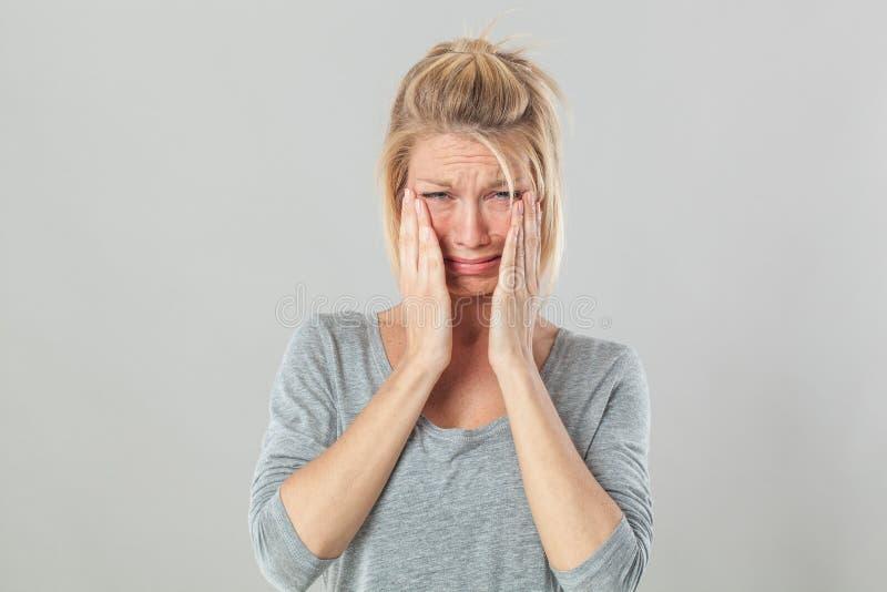 Ledsen blond kvinnagråt som uttrycker förtvivlan, och panikslaget royaltyfria foton