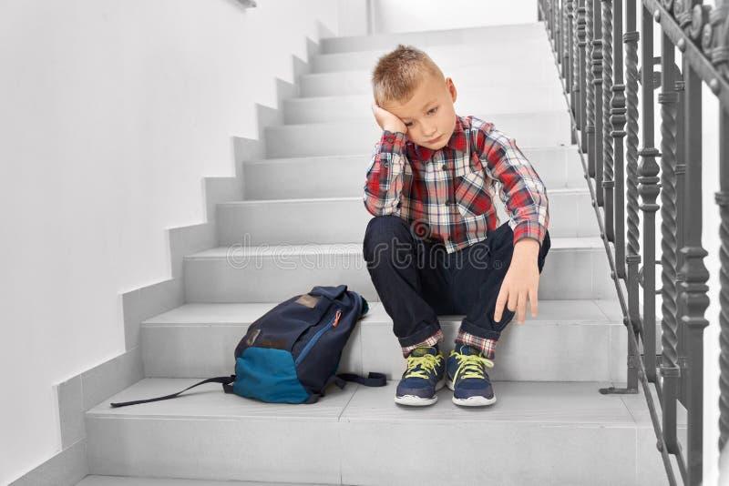 Ledsen blond pojke som sitter på trappa i korridor av skola royaltyfri bild