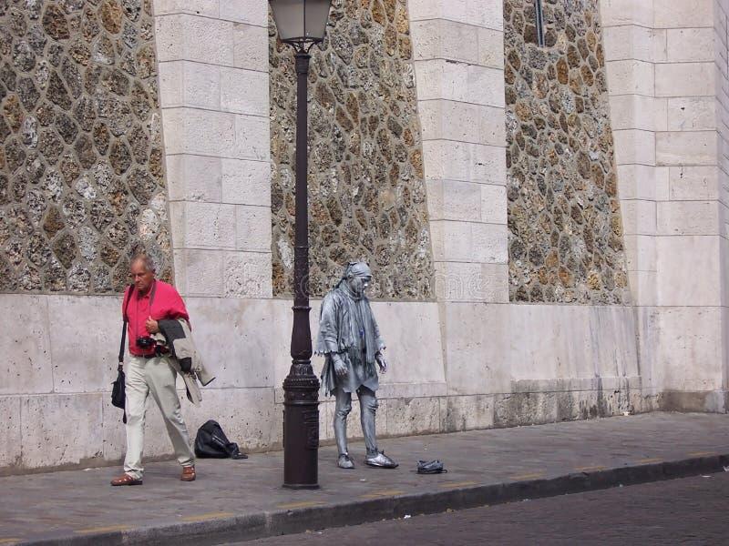 Ledsen bosatt skulptur och en övergående turist Paris, Frankrike-Augusti 05, 2009 royaltyfria foton