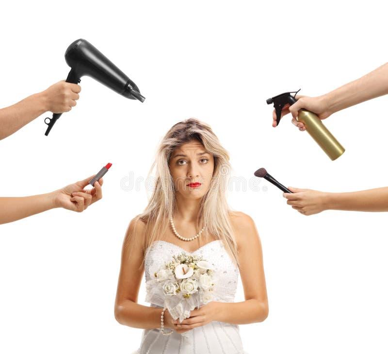 Ledsen brud som väntar på en makeover som omges av händer som rymmer bru royaltyfri foto