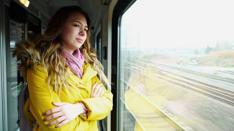 Ledsen charmig kvinnlig resande att sidor och ställningar på drevnea fotografering för bildbyråer