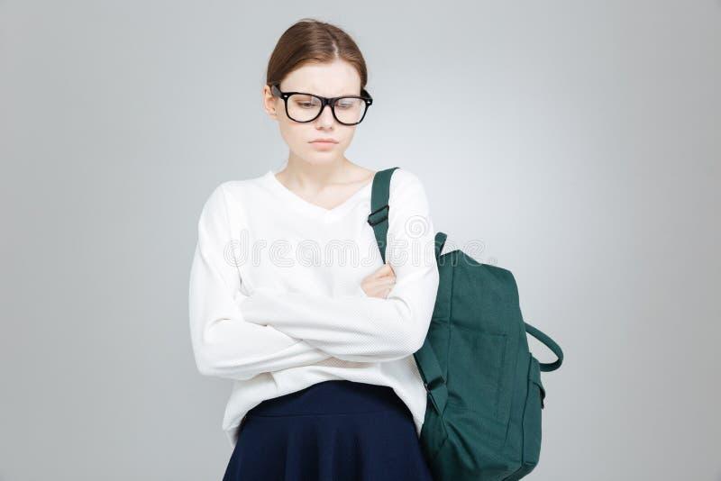 Ledsen deprimerad flickastudent i exponeringsglas som står med vikta händer fotografering för bildbyråer