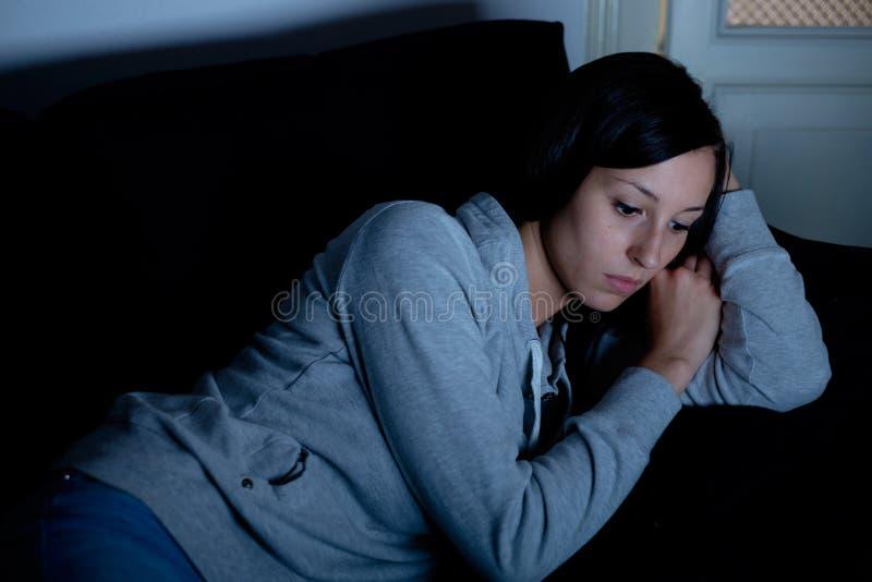 Ledsen deprimerad kvinna som ligger på soffan royaltyfri fotografi