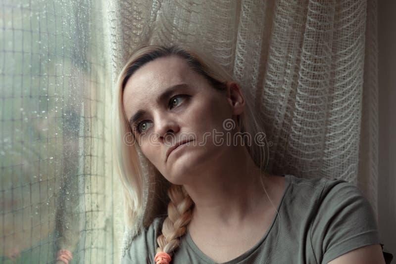 Ledsen deprimerad kvinna som sitter av fönstret som longingly ut ser royaltyfri fotografi