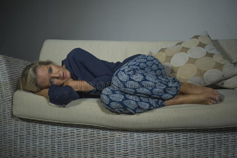 Ledsen deprimerad och angelägen härlig blond soffa för soffa för för kvinnalidandefördjupning och huvudvärk känsla frustrerad lig royaltyfri foto
