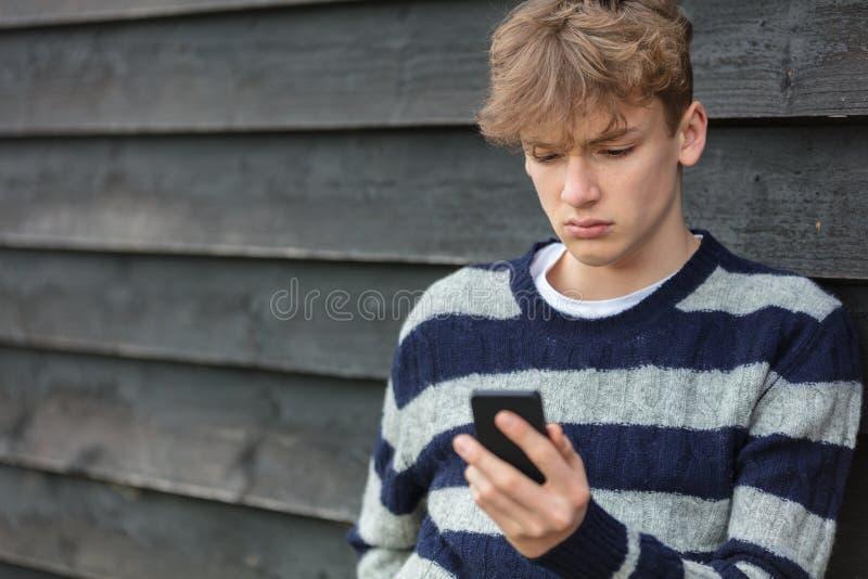 Ledsen deprimerad pojkegossebarntonåring som använder den mobila mobiltelefonen arkivbild