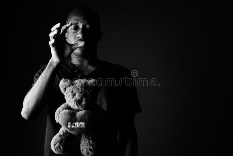 Ledsen deprimerad ung afrikansk man med text för tecken för nallebjörn och förälskelsei svartvitt arkivbilder