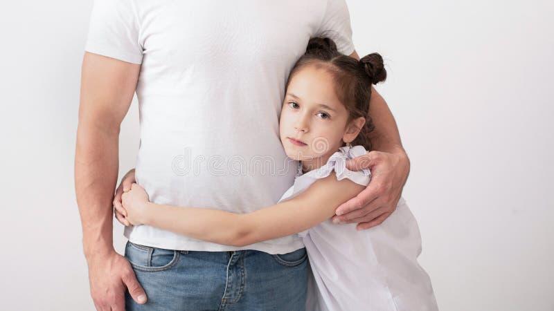 Ledsen dotter som kramar hennes fader, svårigheter mellan föräldrar och barn arkivbild