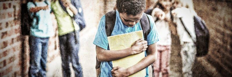Ledsen elev som trakasseras av klasskompisar på korridoren royaltyfri bild