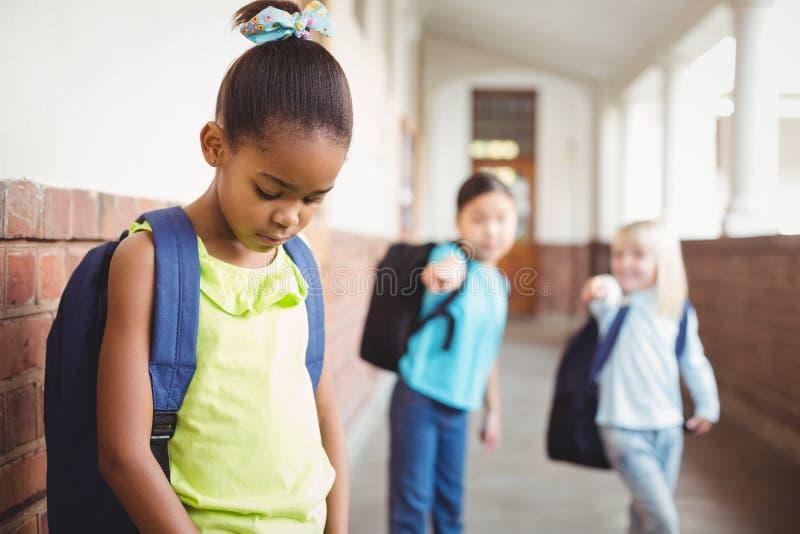 Ledsen elev som trakasseras av klasskompisar på korridoren royaltyfri fotografi