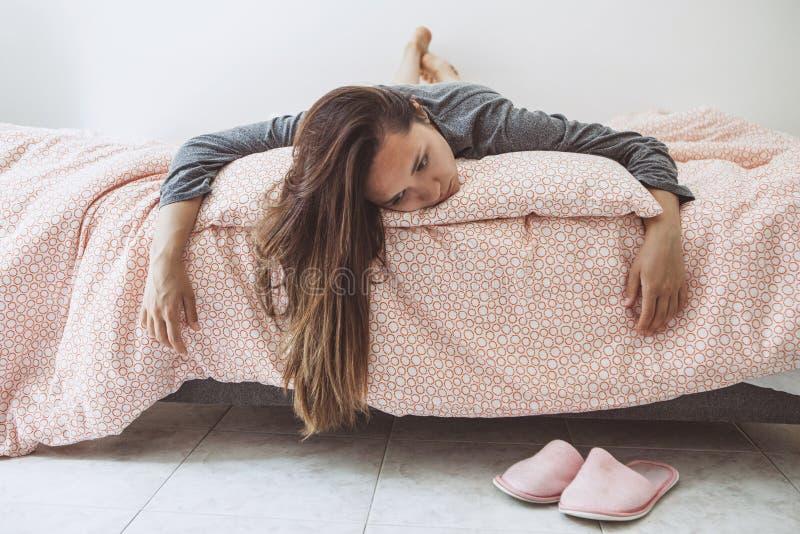 Ledsen eller rubbningflicka som ligger i säng arkivbild