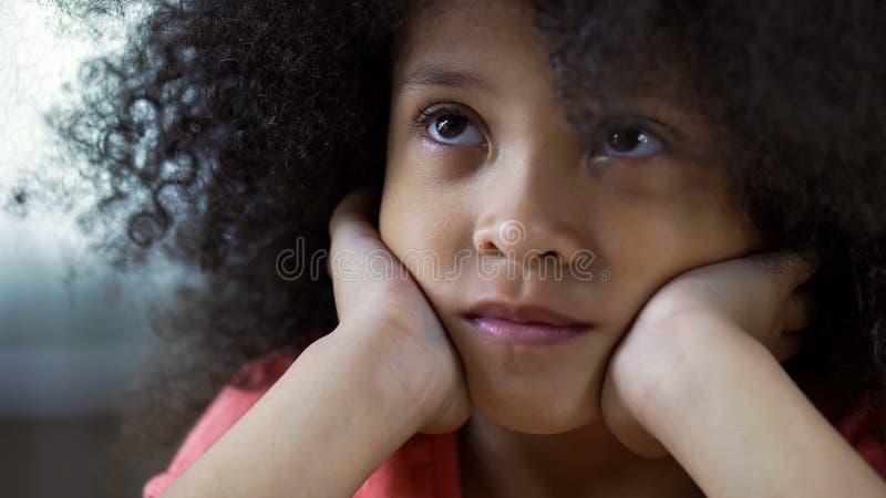 Ledsen ensam afrikansk amerikanflicka som ser upp och tänker om familjen, closeup arkivfoton