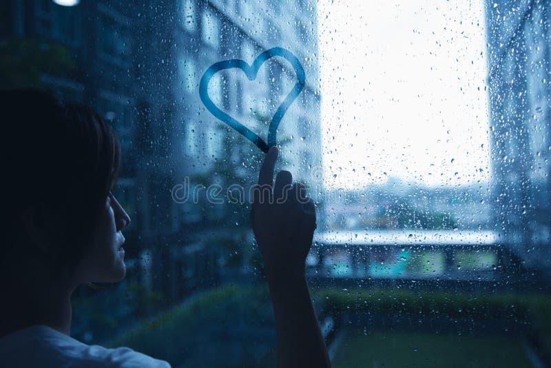 Ledsen ensam förälskelsekvinna i regnattraktionhjärta på fönster royaltyfri bild