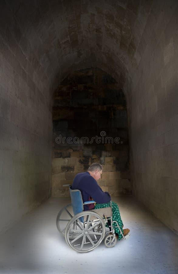 Ledsen ensam hög äldre man i rullstolen som åldras royaltyfri bild