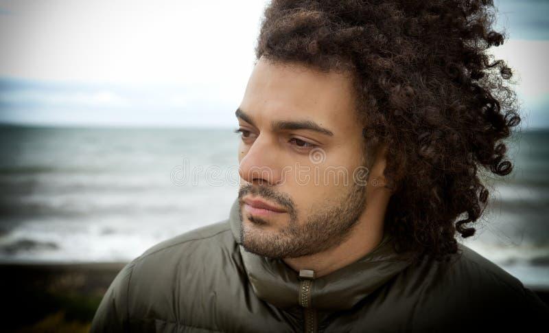 Ledsen ensam man som framme tänker av havet i vinter royaltyfri fotografi