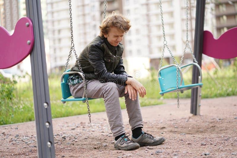 Ledsen ensam ton?ring som ?r utomhus- p? lekplatsen sv?righeterna av ton?rstid i kommunikationsbegrepp arkivfoton