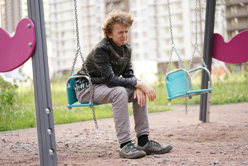 Ledsen ensam ton?ring som ?r utomhus- p? lekplatsen sv?righeterna av ton?rstid i kommunikationsbegrepp arkivbilder