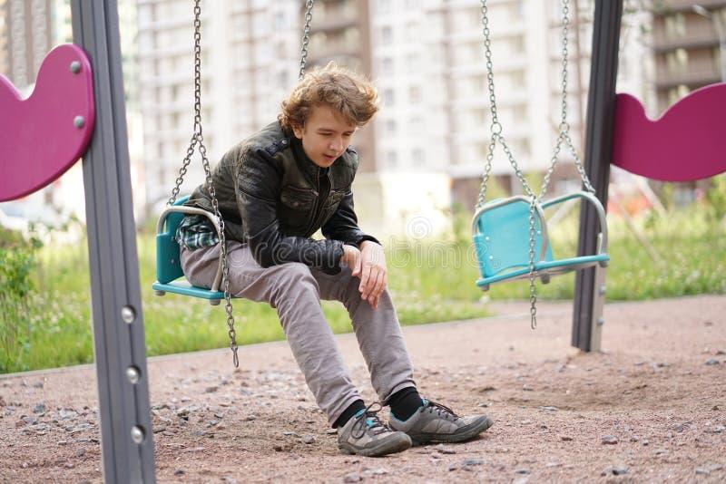 Ledsen ensam ton?ring som ?r utomhus- p? lekplatsen sv?righeterna av ton?rstid i kommunikationsbegrepp royaltyfri fotografi