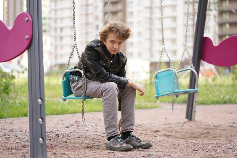 Ledsen ensam ton?ring som ?r utomhus- p? lekplatsen sv?righeterna av ton?rstid i kommunikationsbegrepp fotografering för bildbyråer