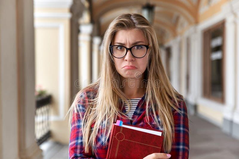 Ledsen förbryllad ung flickatonåringstudent med exponeringsglas som rymmer en bok med ett olyckligt ledset uttryck royaltyfri foto