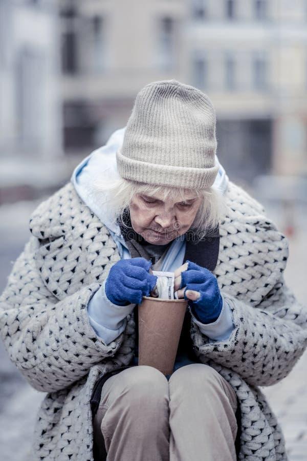 Ledsen fattig kvinna som ser pengarna arkivbild