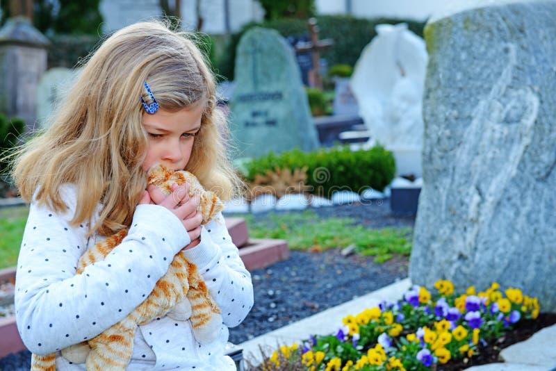 Ledsen flicka framme av graven arkivbild