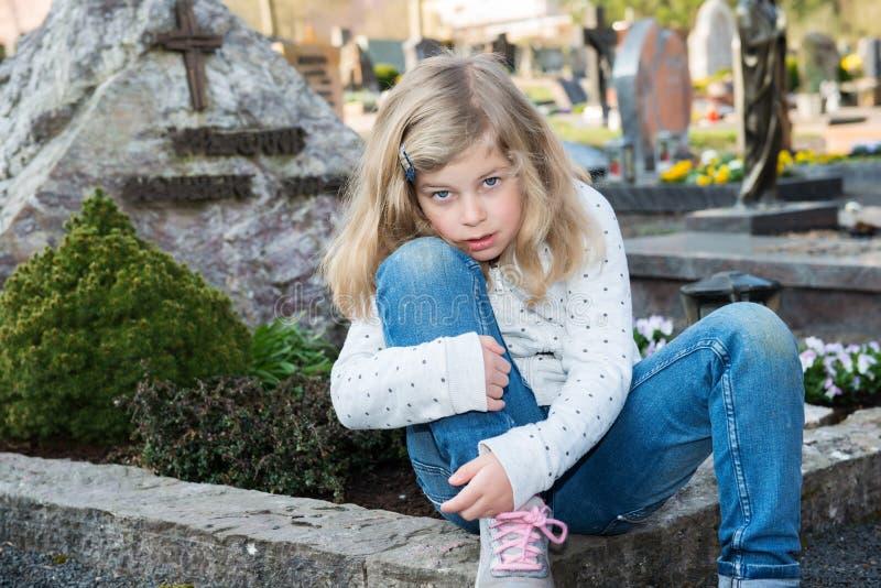 Ledsen flicka framme av graven royaltyfri fotografi