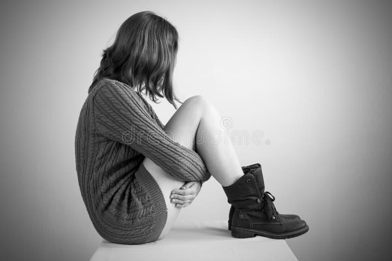 Ledsen flicka i en tröja arkivfoto