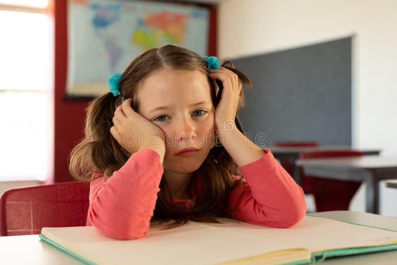 Ledsen flicka som lutar på skrivbordet i ett klassrum arkivbilder