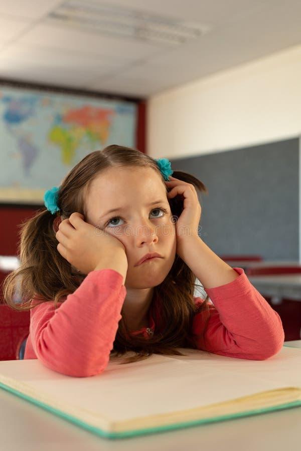 Ledsen flicka som lutar på skrivbordet i ett klassrum på skola royaltyfri bild
