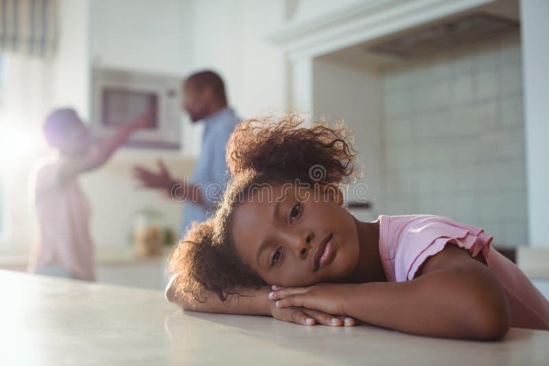 Ledsen flicka som lyssnar till hennes föräldrar som argumenterar i kök arkivbild