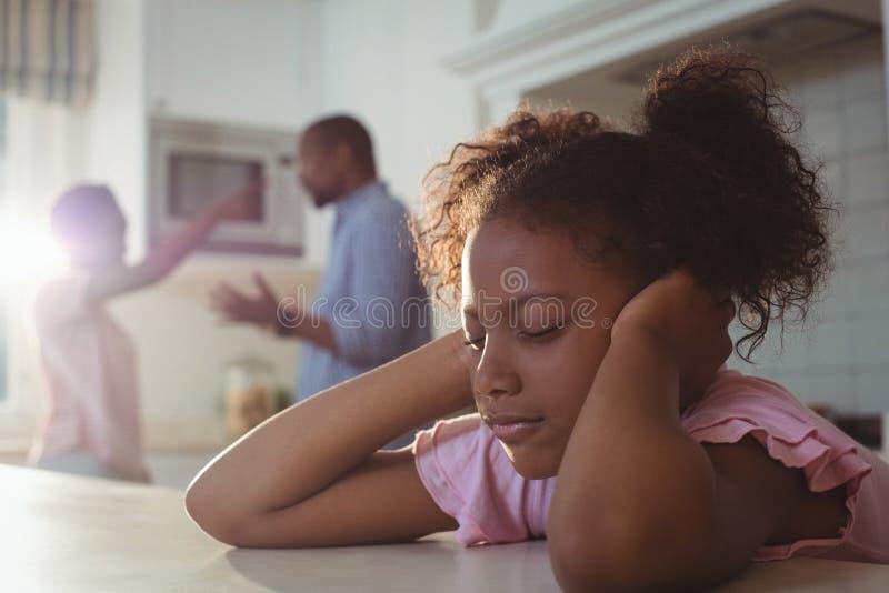 Ledsen flicka som matas upp av hennes föräldrar som argumenterar i kök arkivfoto
