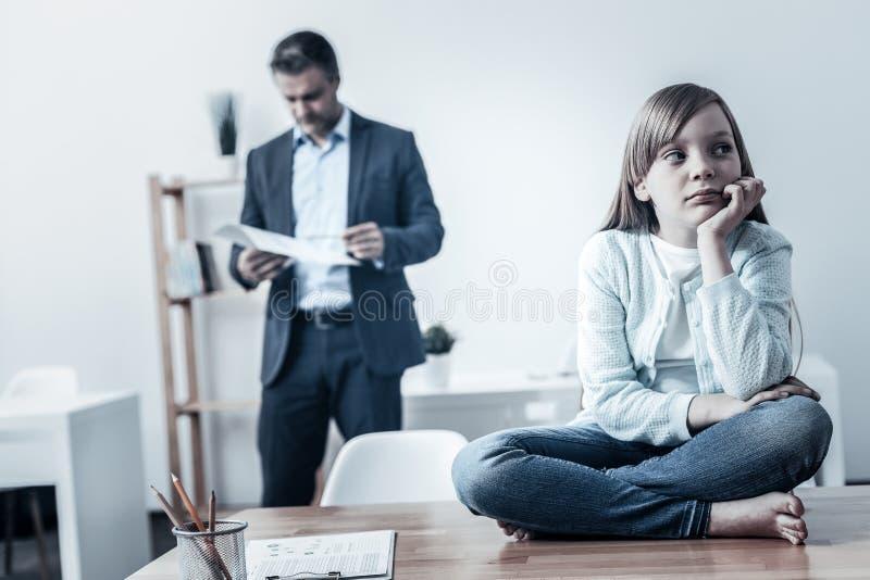 Ledsen flicka som missa hennes upptagna arbete för pappa i bakgrund royaltyfria foton